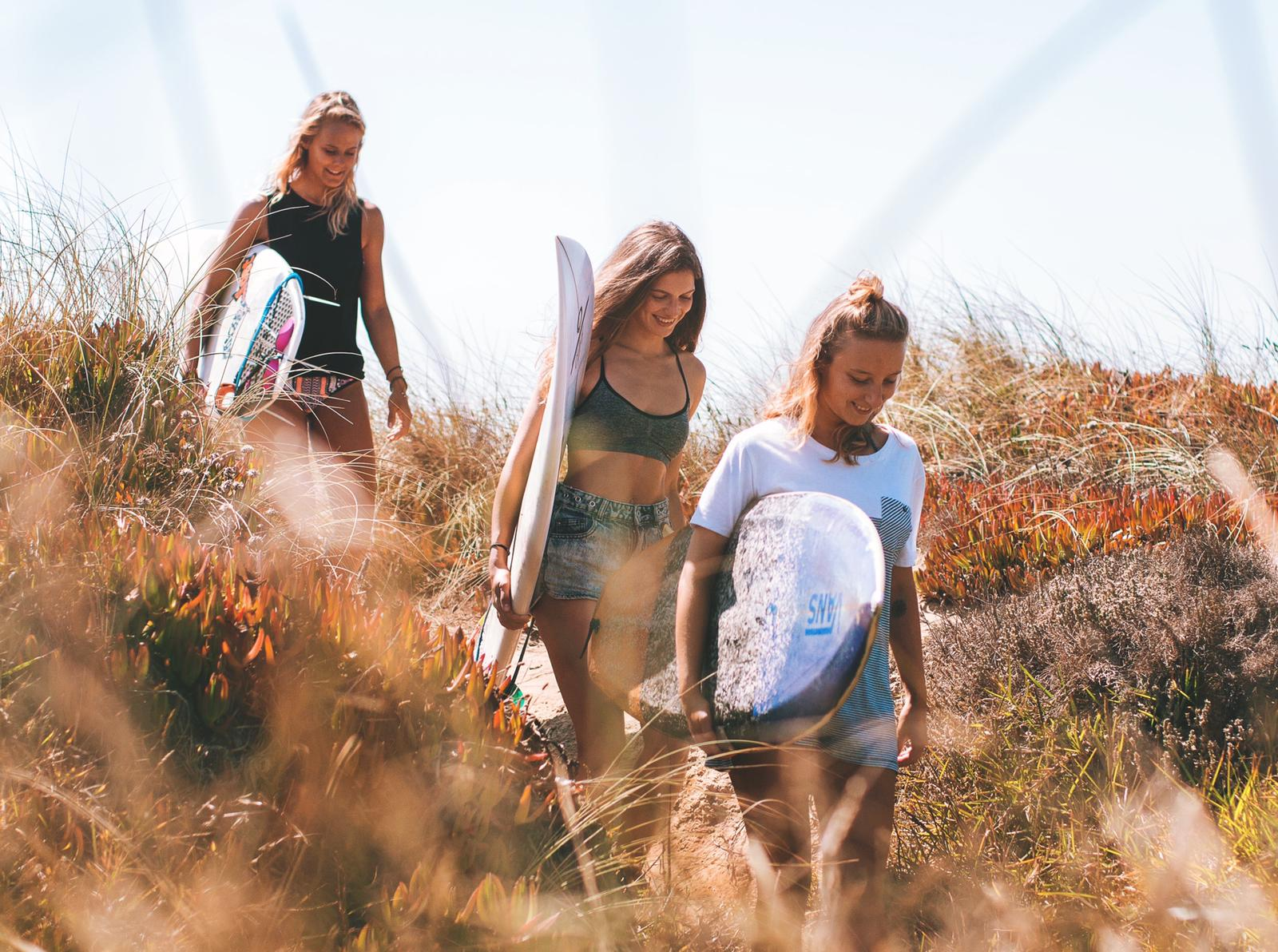 three girls walking down to the beach