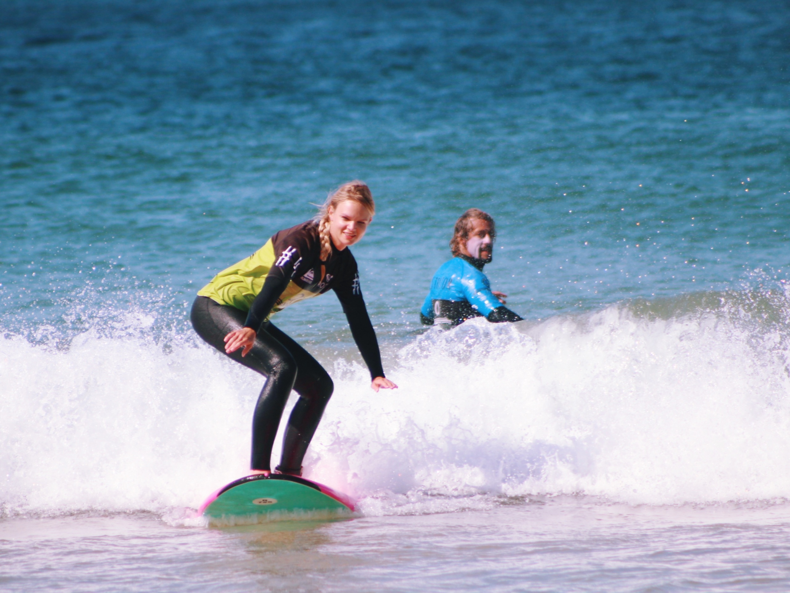 surf coach teaching a woman in surfing