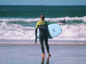 surf coach walking into the waves