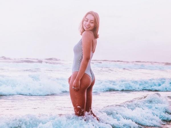 Girl from a photoshoot standing in bikini in the ocean