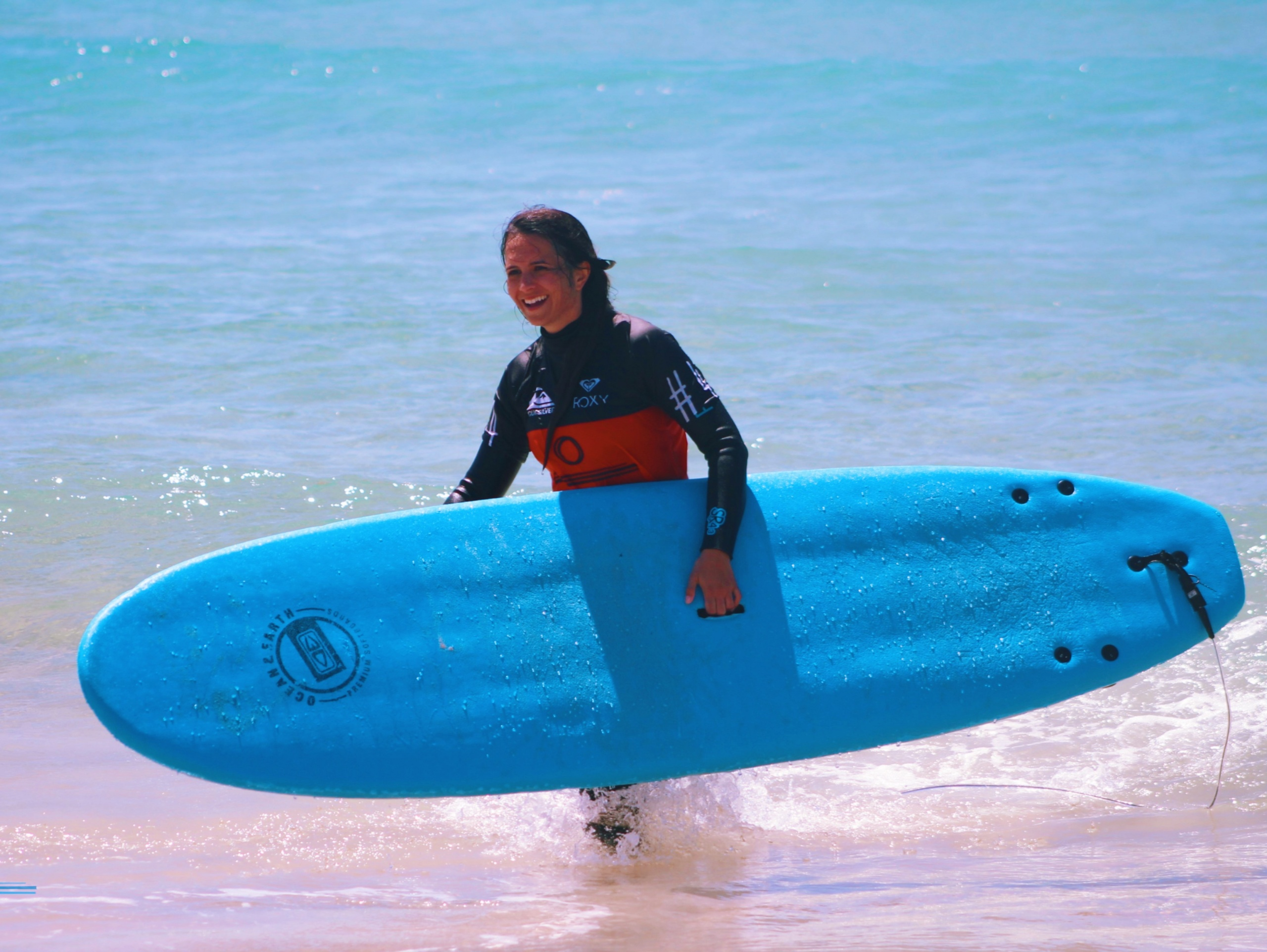 Surfer girl walking with a board