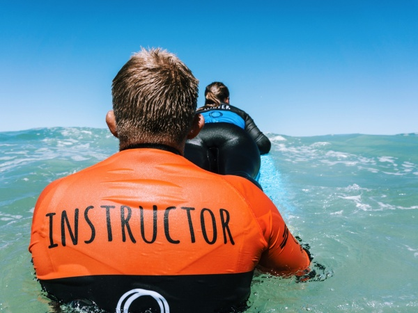 surf instructor from the back pushing a guest