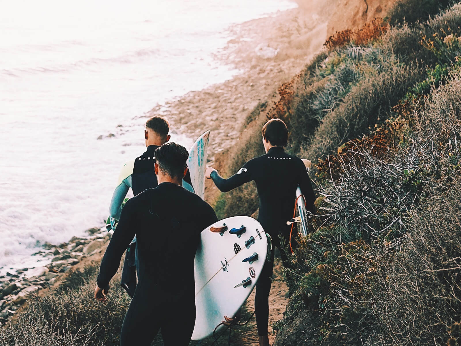 boys crew walking for a surf session