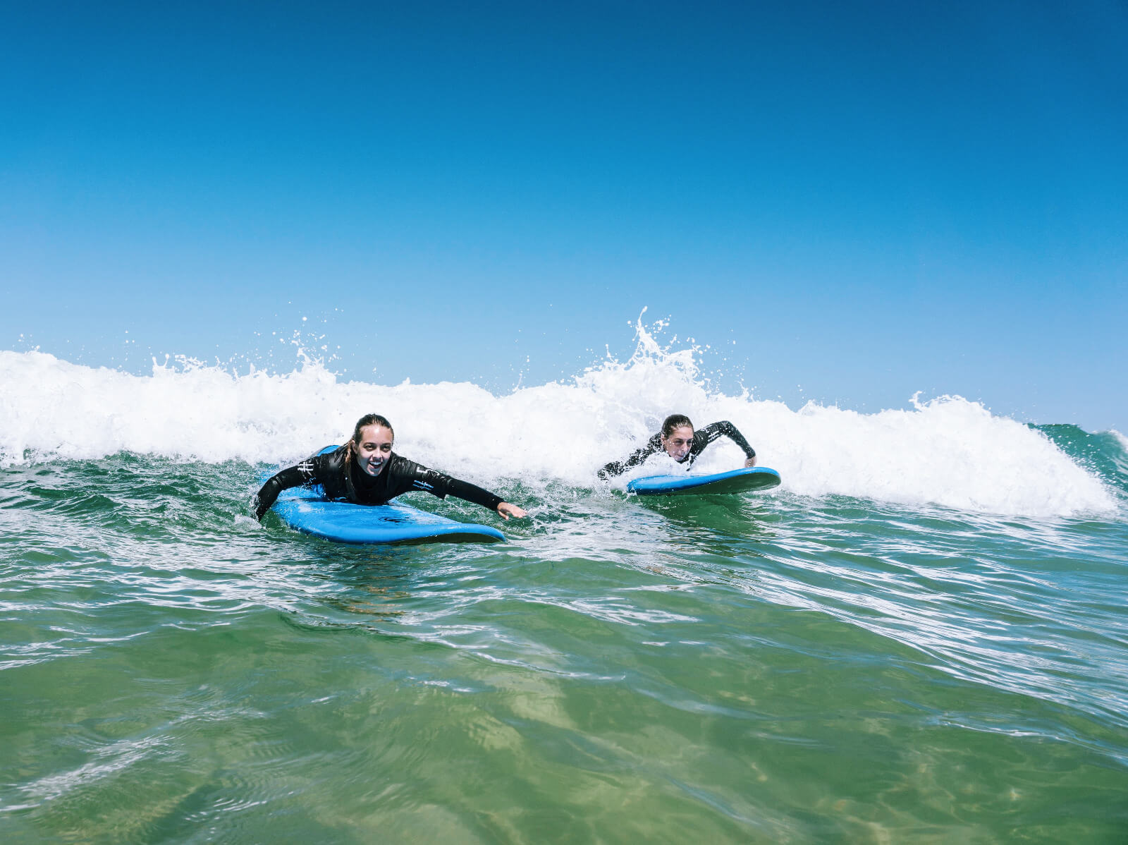 Two girls surfing