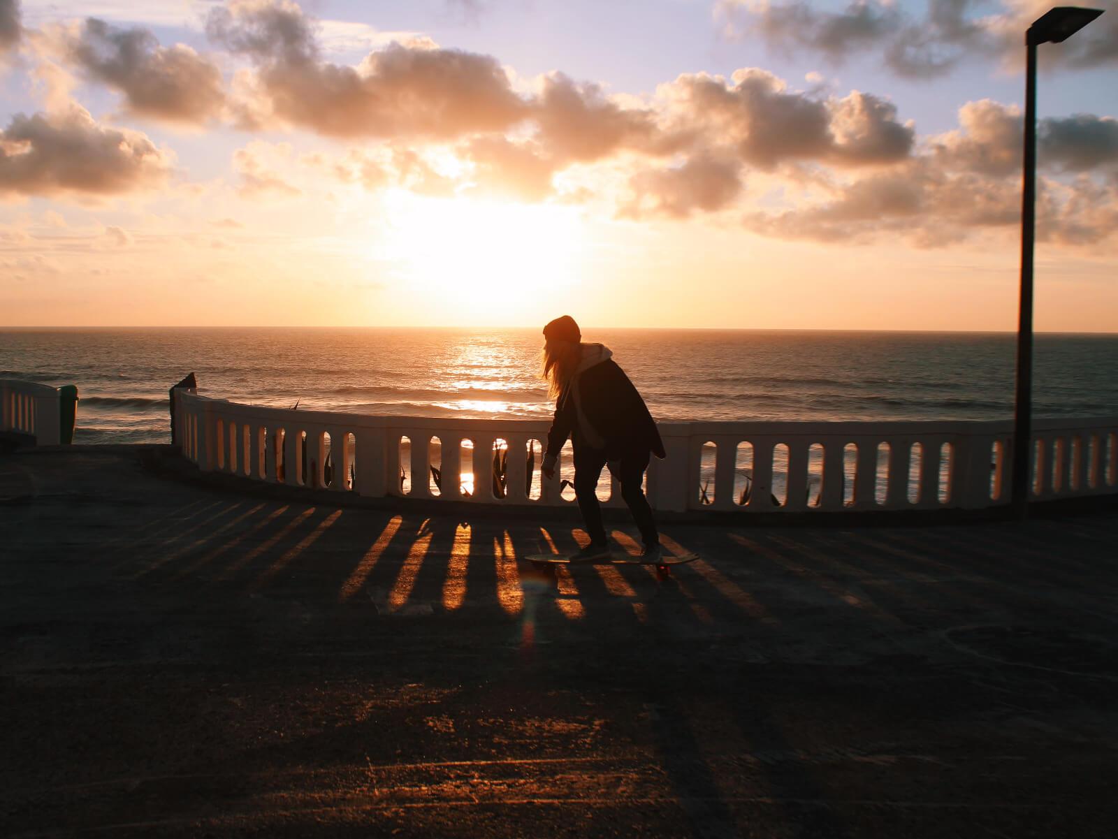 Skateboarder at sunset in santa cruz portugal