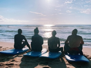 4 people sitting on a surfboard watching the ocean
