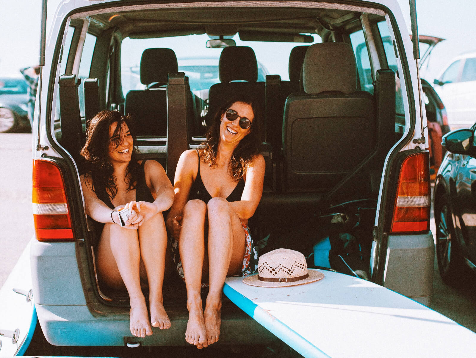 2 girls sitting in the back of a surf van