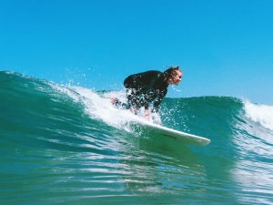 Surfer girl going down the wave and having fun