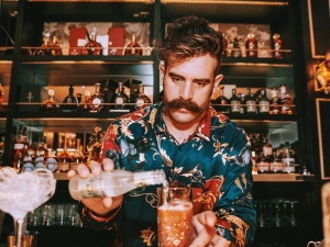 Handsome guy serving drinks at the bar